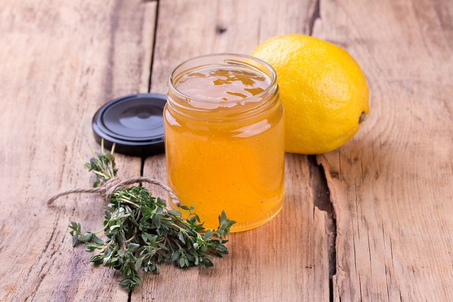 Colorful citrus jam in glass jar thyme and lemon on rustic wooden board