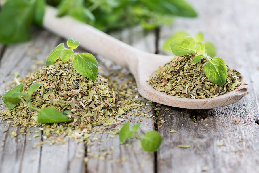 Oregano on a wooden spoon (against wooden background) ** Note: Shallow depth of field