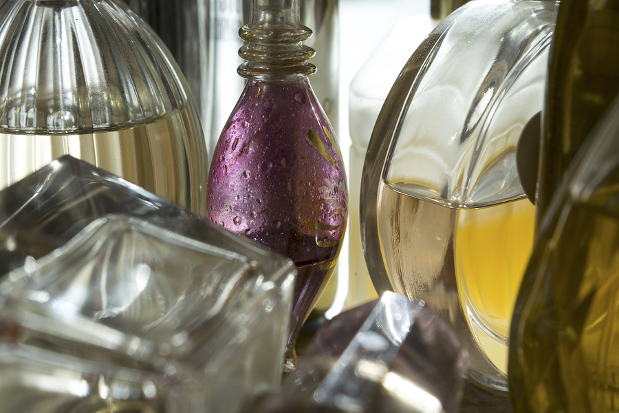 closeup of a series of small bottles of perfume in backlight