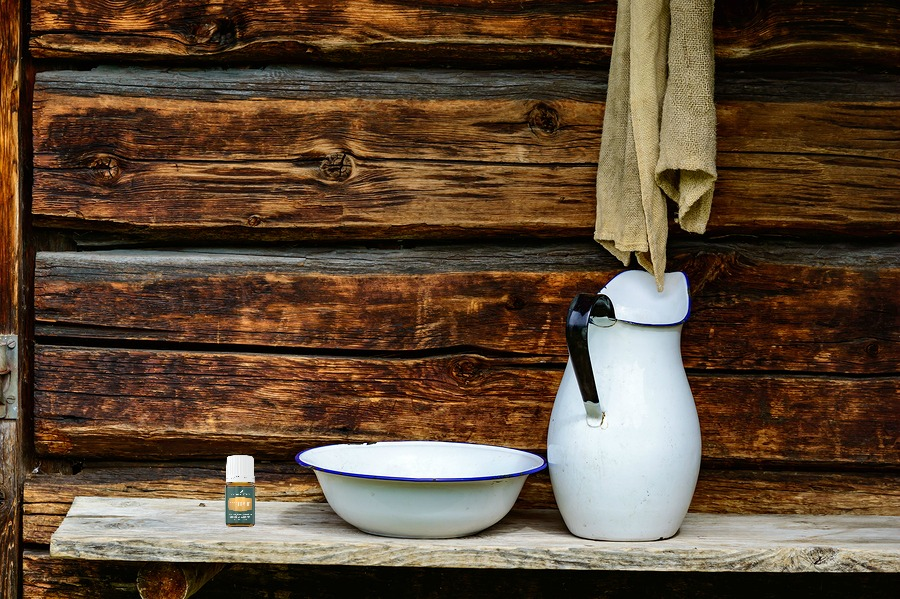 Place to wash up with white jug and bowl for water and a rugged cloth to dry with. Timber facade with copy space.