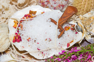 Healthy marine bath salts rich in minerals mixed with dried aromatic rose petals for a luxury bath treatment at a spa