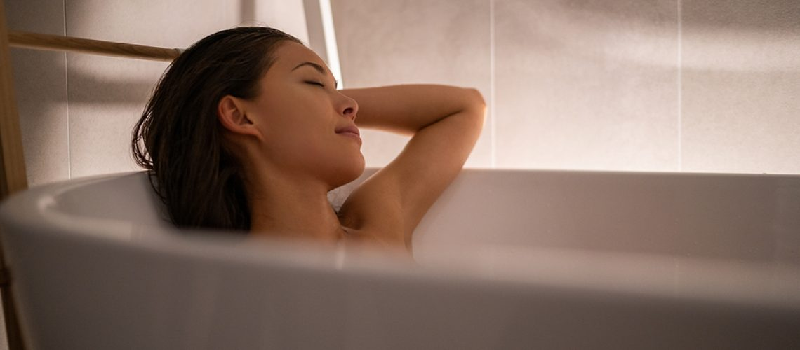 Luxury bath woman relaxing in hotel spa bathtub or home bathroom