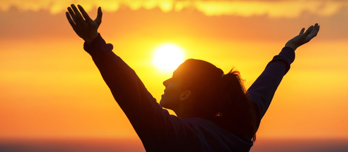 Free woman raising arms to golden sunset summer sky like praising. Freedom success and hope concept. Girl relaxing and enjoying peace and serenity on beautiful nature.