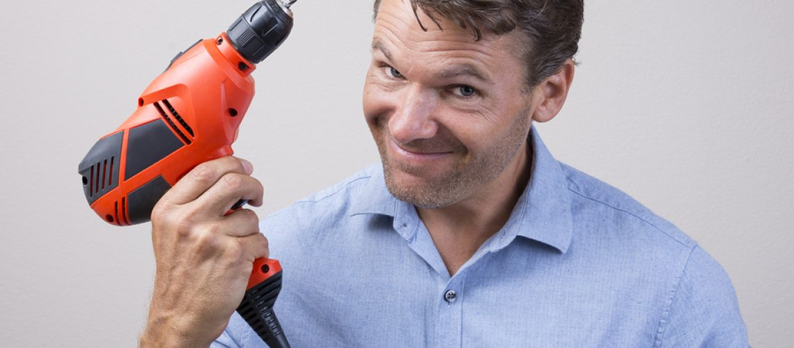 Closeup of handsome Caucasian man holding electric power drill with expression of readiness looking into camera