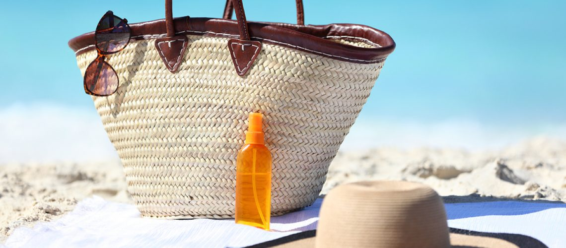 Women's beach accessories on sand for summer vacation concept. Straw tote bag, sun hat and sunscreen lotion or suntan tanning oil spray bottle with blue ocean background for travel holidays.