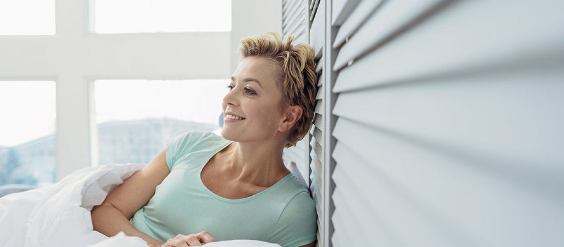 Dreamful woman is relaxing on bed at home. She is laughing