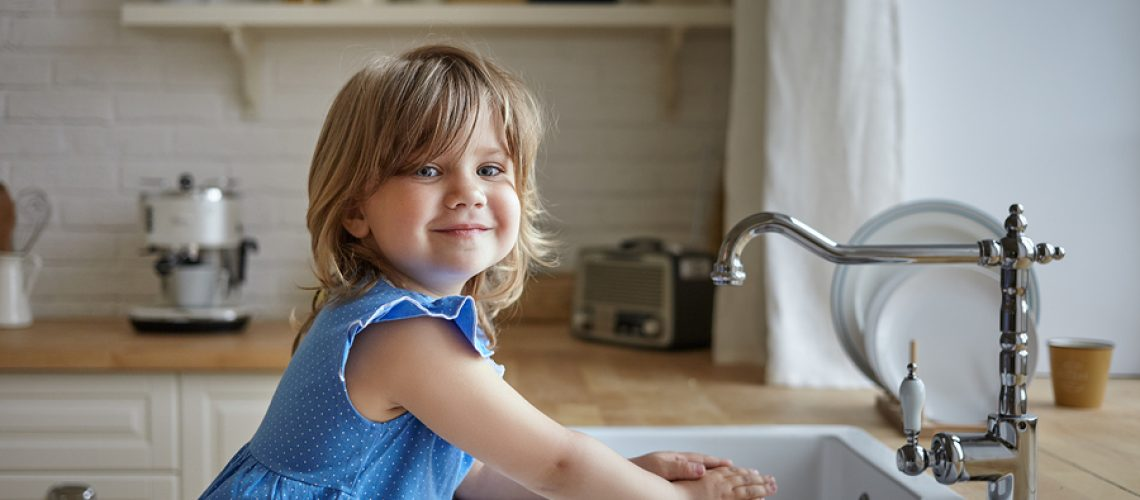 Charming little girl in blue dress washing hands in kitchen. Cute female kid looking and smiling at camera, helping mother, doing dishes, standing at sink. Kids, childhood, cooking and housework